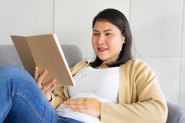 Femme enceinte asiatique allongée sur le canapé et lisant un livre