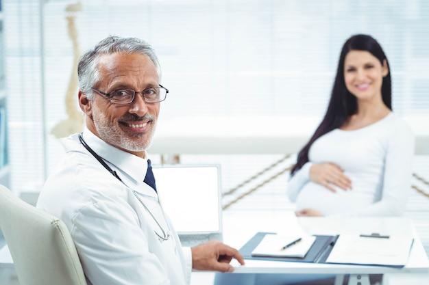 Femme enceinte assise avec un médecin à la clinique pour un bilan de santé