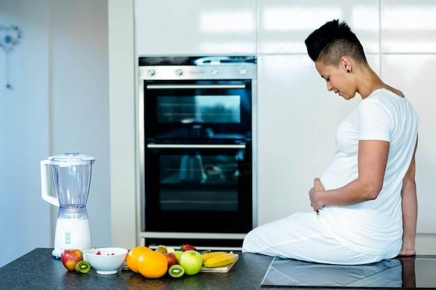 Femme enceinte assise sur le plan de travail de la cuisine et regardant son ventre