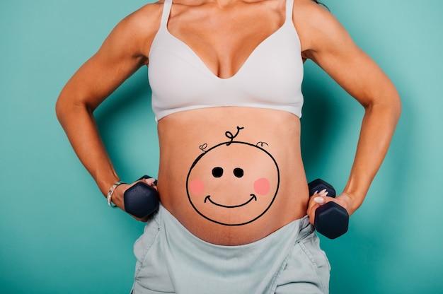 La femme enceinte attendant un enfant caresse son ventre