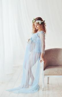 Femme enceinte aux cheveux bouclés et une guirlande de fleurs sur sa tête