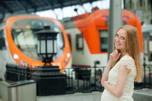 La femme enceinte aux cheveux longs attend le train