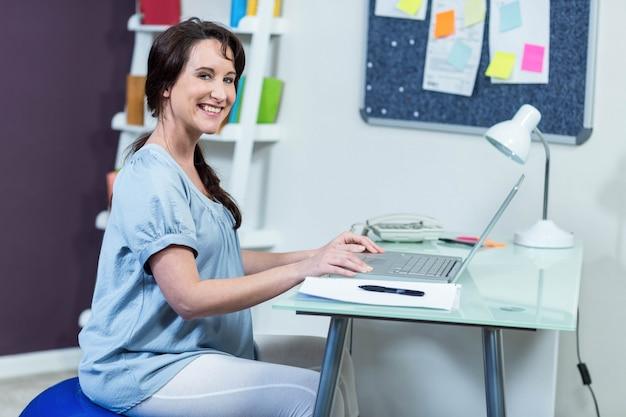 Femme enceinte sur ballon d'exercice à l'aide d'un ordinateur portable
