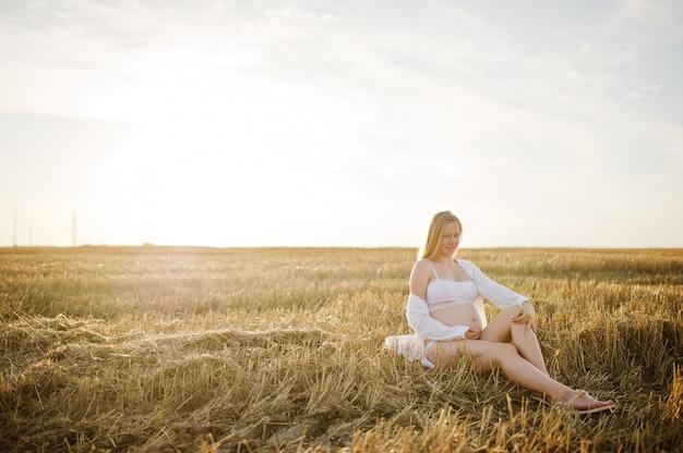 Femme enceinte blonde dans le champ de la gerbe au coucher du soleil