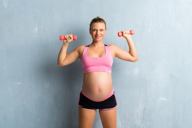 Femme enceinte blonde faisant du sport en haltérophilie