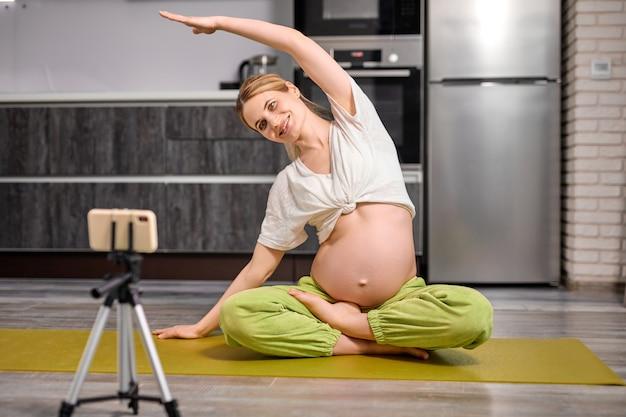 Une femme enceinte blonde flexible et caucasienne fait des exercices de yoga en regardant une vidéo en ligne