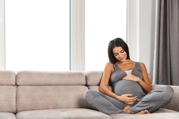 Femme enceinte en bonne santé à l'intérieur à la maison assis posant.