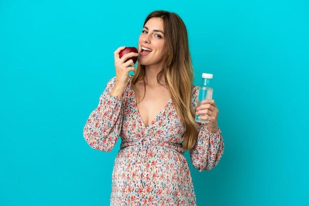 Femme enceinte avec une bouteille d'eau et manger une pomme