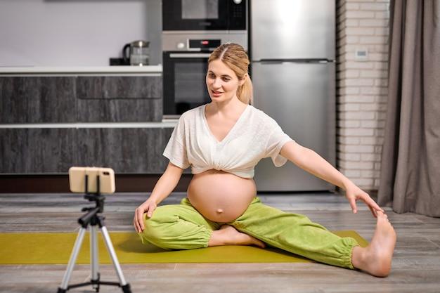 Une femme enceinte caucasienne assez blonde fait des exercices de yoga en regardant une vidéo en ligne