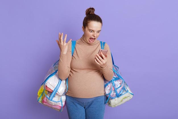 Femme enceinte en colère avec téléphone portable dans les mains avec une expression faciale en colère