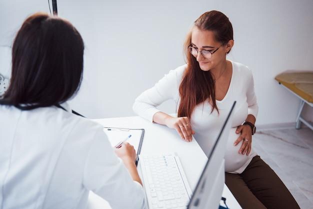 Une femme enceinte consulte un obstétricien à l'intérieur.