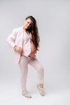 Femme enceinte en costume rose gros plan sur fond gris