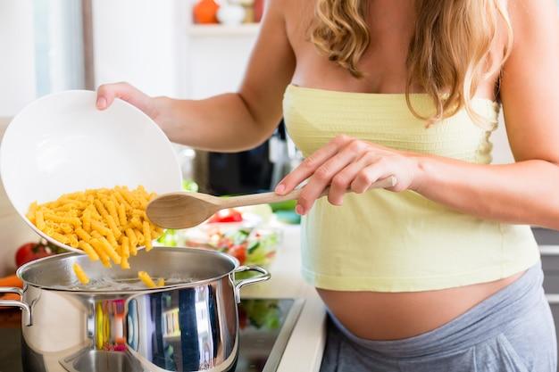 Femme enceinte, cuisiner des pâtes dans la cuisine domestique