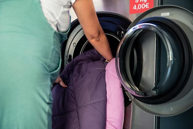 Femme enceinte dans une blanchisserie. mettre les vêtements à laver dans la machine à laver.