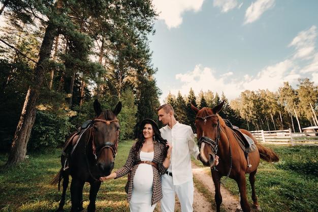 Une femme enceinte dans un chapeau avec un homme en vêtements blancs marchant avec des chevaux dans la nature.
