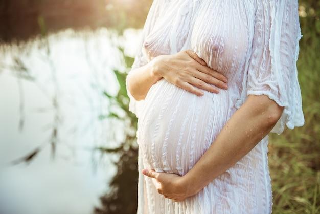 Femme enceinte dans le parc extérieur par temps chaud. concept de grossesse - femme enceinte tenant sur le ventre gros plan sur fond d'été ensoleillé