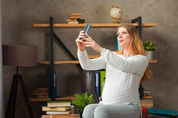 Femme enceinte dans un pull blanc. une blogueuse enceinte prend un selfie au téléphone.