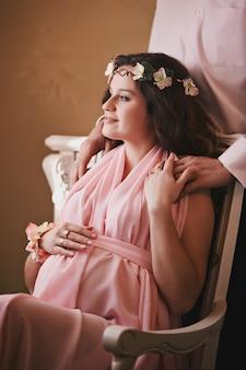 Femme enceinte dans une robe rose assise sur une chaise derrière un homme souriant debout
