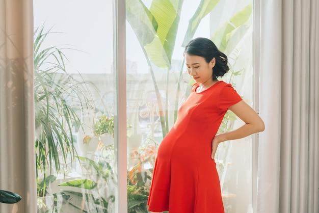 Femme enceinte, debout, contre, fenêtre