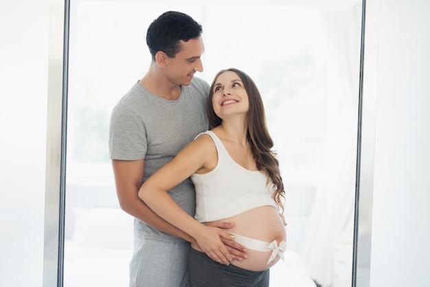 Femme enceinte et derrière elle se tient l'homme et lui serre le ventre.