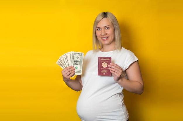 Femme enceinte détenant un passeport avec de l'argent. avantages pour les femmes enceintes, sur mur jaune