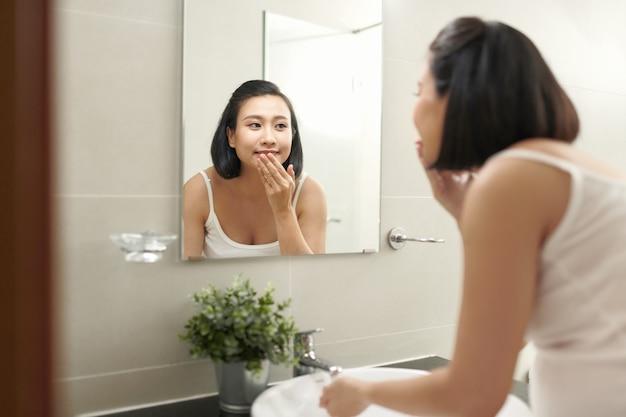 Femme enceinte éclaboussant le visage avec de l'eau au-dessus du lavabo de la salle de bain