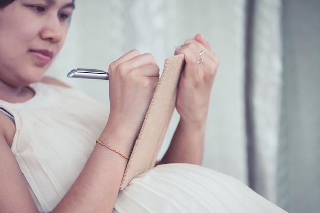 Femme enceinte écrit dans un cahier pour énumérer les choses nécessaires à la naissance et au bébé