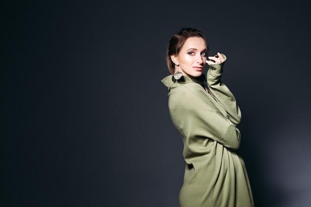 Femme enceinte élégante posant au studio sombre.