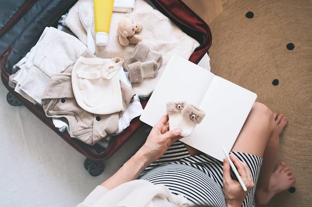 Femme enceinte emballant un sac d'hôpital avec une liste de contrôle