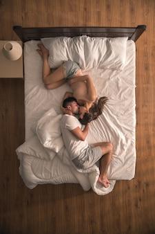 La femme enceinte embrasse un homme sur le lit. vue d'en-haut