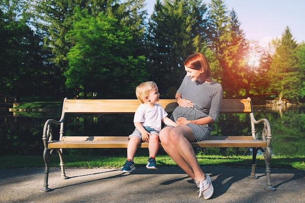 Femme enceinte avec enfant à l'extérieur mère et fils sur la nature dans le parc d'été