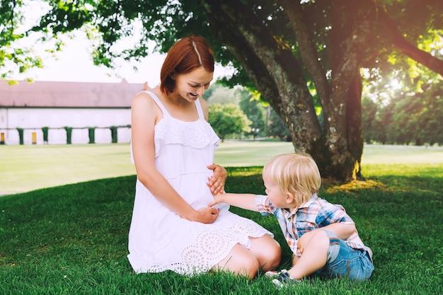 Femme enceinte avec enfant sur la nature mère et fils parlent et passent du temps ensemble à l'extérieur