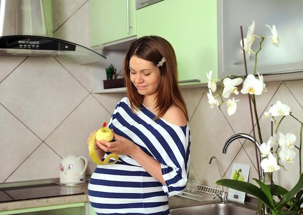 La femme enceinte épluche la pomme.