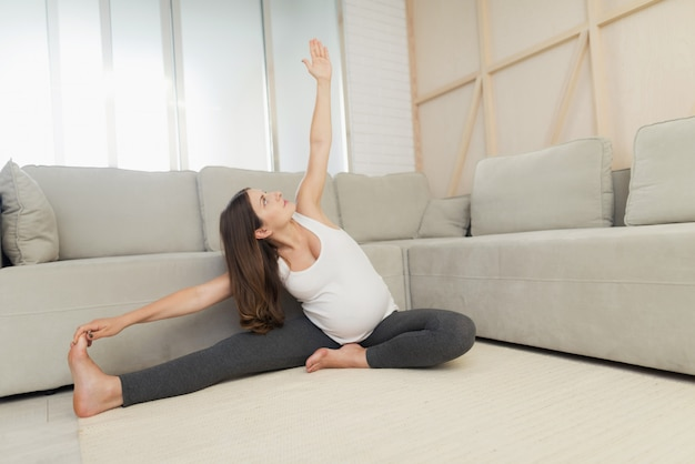 Une femme enceinte est assise à la maison sur un sol léger.