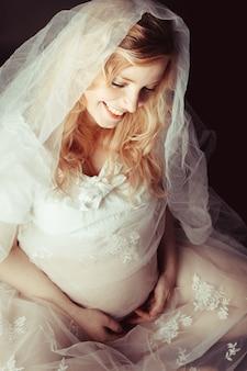 La femme enceinte est assise et rêve de bébé