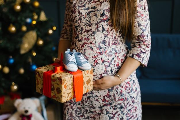 Une femme enceinte est titulaire d'une boîte-cadeau avec un ruban rouge et des baskets pour bébé près de son ventre dans le contexte d'un arbre de noël
