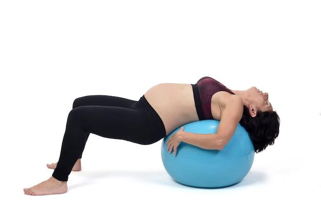 Femme enceinte exerçant avec un ballon sur fond blanc