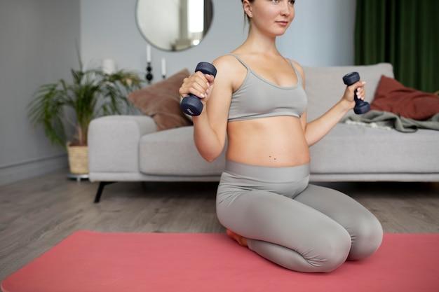 Femme enceinte exerçant à la maison
