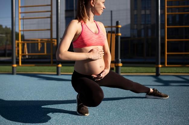 Femme enceinte exerçant seule à l'extérieur