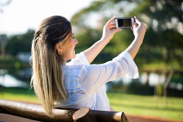 Femme enceinte faisant autoportrait à l'aide de smartphone
