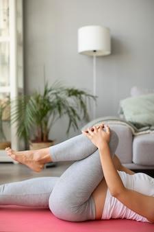 Femme enceinte faisant du yoga à la maison