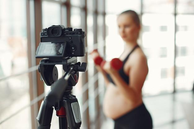 Une femme enceinte fait du sport avec des dambbels