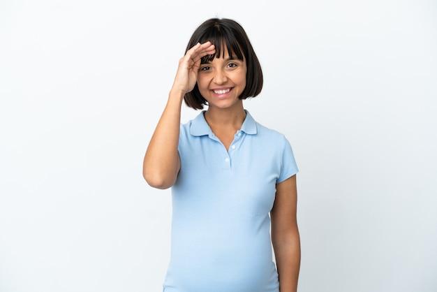 Femme enceinte sur fond blanc isolé saluant avec la main avec une expression heureuse