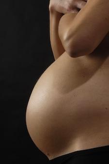 Femme enceinte avec un fond noir