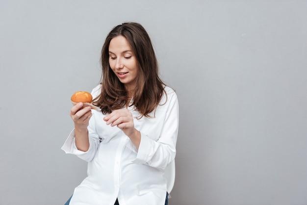 Femme enceinte avec gâteau fond gris isolé