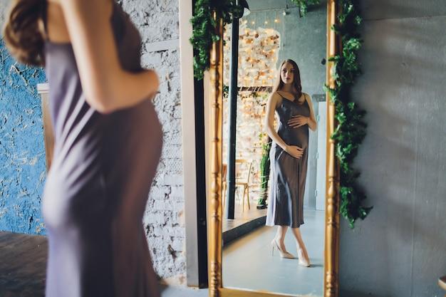 Une femme enceinte heureuse regarde avec amour un reflet d'elle-même et de son bébé à naître dans un miroir.