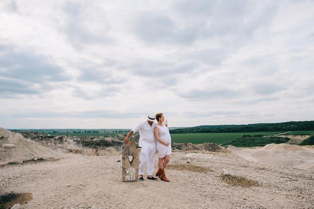 Femme enceinte et homme assis sur un rocher