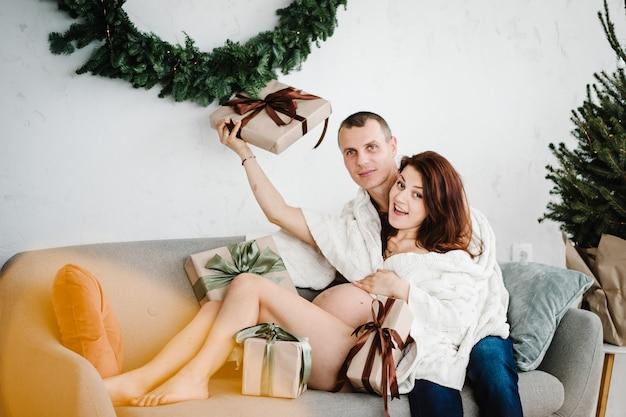 Femme enceinte et homme couvert de plaid près de l'arbre de noël à la maison beaucoup de cadeaux famille