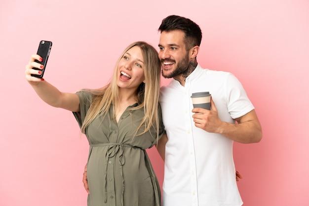 Femme enceinte et homme sur fond rose isolé faisant un selfie avec le mobile