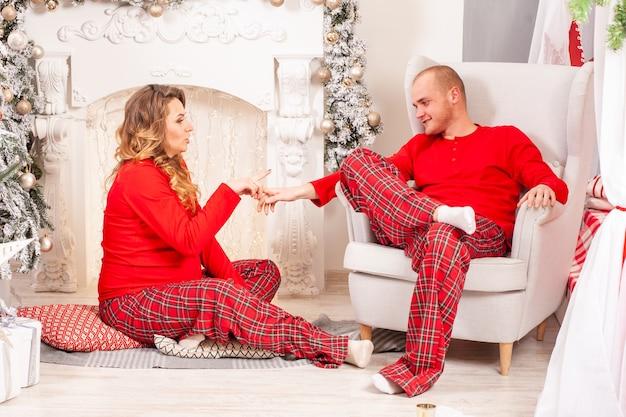Une femme enceinte et un homme heureux s'amusent à l'intérieur de noël